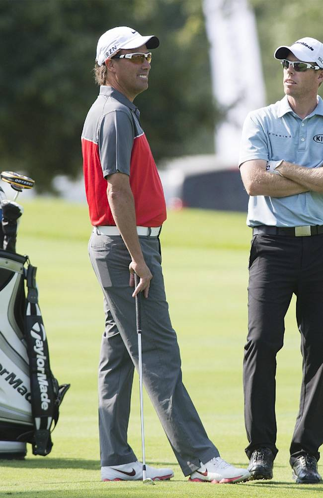 Stephen Ames, left, and David Hearn, of Canada, chat during a practice round for the 2014 RBC Canadian Open golf tournament at the Royal Montreal Golf Club in Montreal, Monday, July 21, 2014