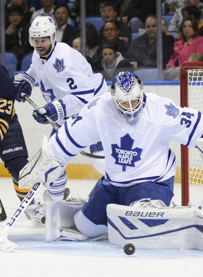 Buffalo Sabres' Ville Leino (23) looks for a rebound from Toronto Maple Leafs goalie James Reimer (34) as Leafs' Mark Fraser (2) defends during first period of an NHL hockey preseason game in Buffalo, N.Y., Saturday, Sept. 21, 2013