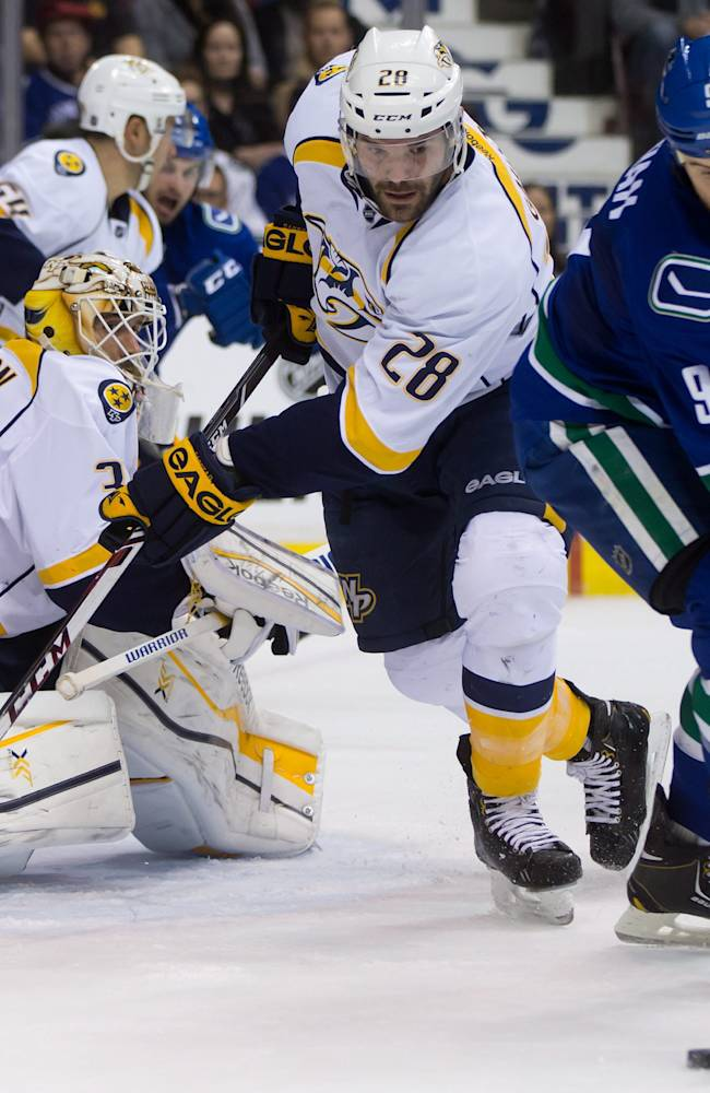 Vancouver Canucks' Zack Kassian, right, attempts a shot against Nashville Predators goalie Carter Hutton, left, as Paul Gaustad defends during first-period NHL hockey game action in Vancouver, British Columbia, Wednesday, March 19, 2014