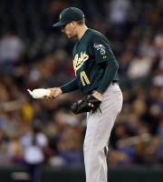 Oakland Athletics starting pitcher Jarrod Parker grabs the rosin bag after giving up a solo home run to Seattle Mariners' Brad Miller during the third inning of a baseball game in Seattle, Saturday, Sept. 28, 2013. (AP Photo/John Froschauer)