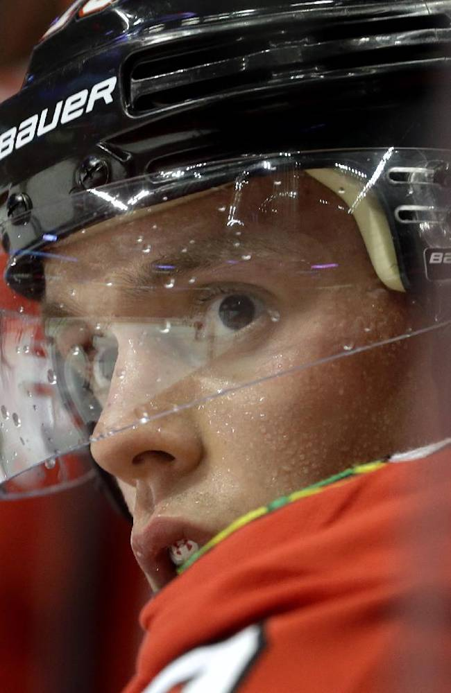 Chicago Blackhawks' Jonathan Toews (19) watches his teammates play during the second period of an NHL preseason hockey game against the Washington Capitals in Chicago, Saturday, Sept. 28, 2013