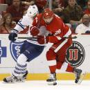 Toronto Maple Leafs defenseman Jake Gardiner (51) and Detroit Red Wings right wing Tomas Jurco (26) battle for the puck in the second period of a NHL hockey game in Detroit Monday, Sept. 29, 2014. (AP Photo/Paul Sancya)