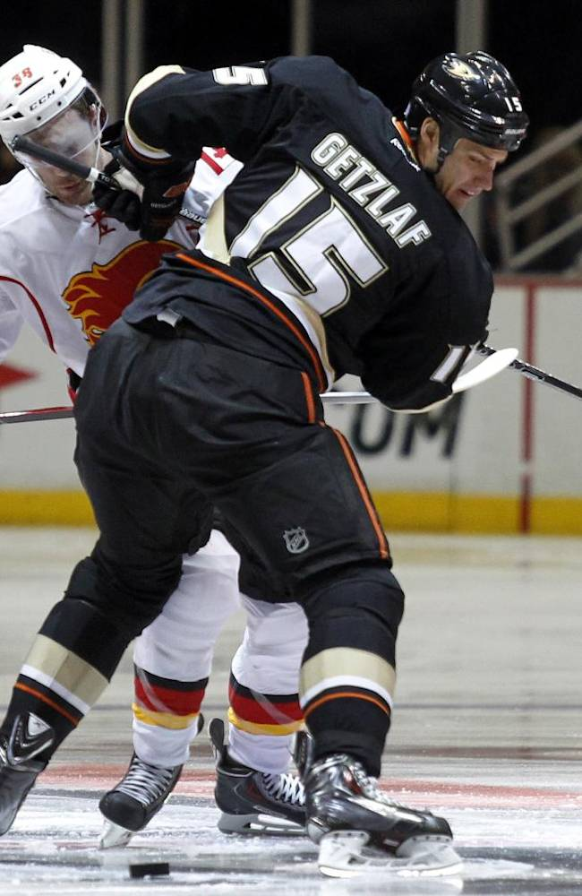 Anaheim Ducks center Ryan Getzlaf (15) stops Calgary Flames right wing Ben Street, left, from getting to the puck during the first period of an NHL hockey game, Wednesday, Oct. 16, 2013, in Anaheim, Calif