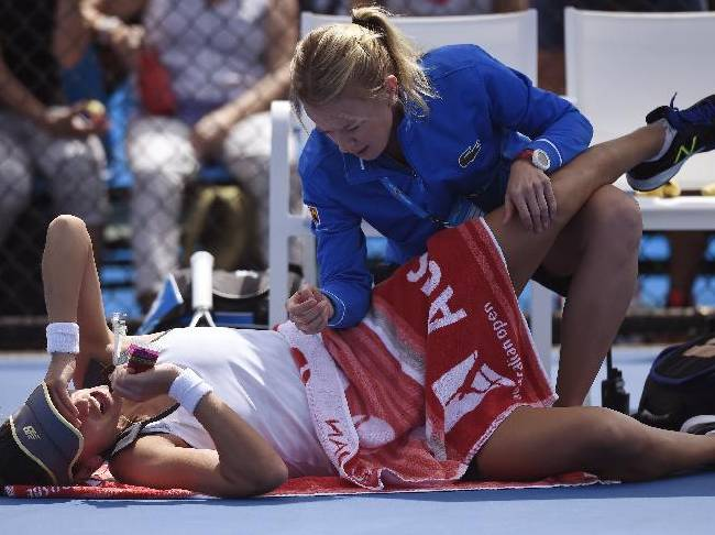Chanelle Scheepers of South Africa receives treatment from a trainer as she plays Anna Schmiedlova of Slovakia v during their first round match at the Australian Open tennis championship in Melbourne, Australia, Monday, Jan. 19, 2015