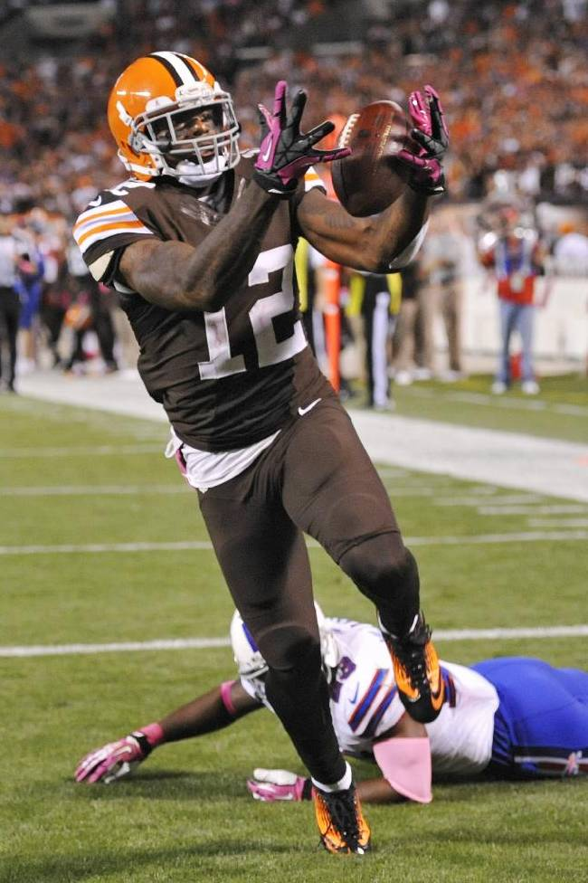 Cleveland Browns wide receiver Josh Gordon (12) grabs a 37-yard touchdown pass against Buffalo Bills free safety Aaron Williams in the third quarter of an NFL football game Thursday, Oct. 3, 2013, in Cleveland