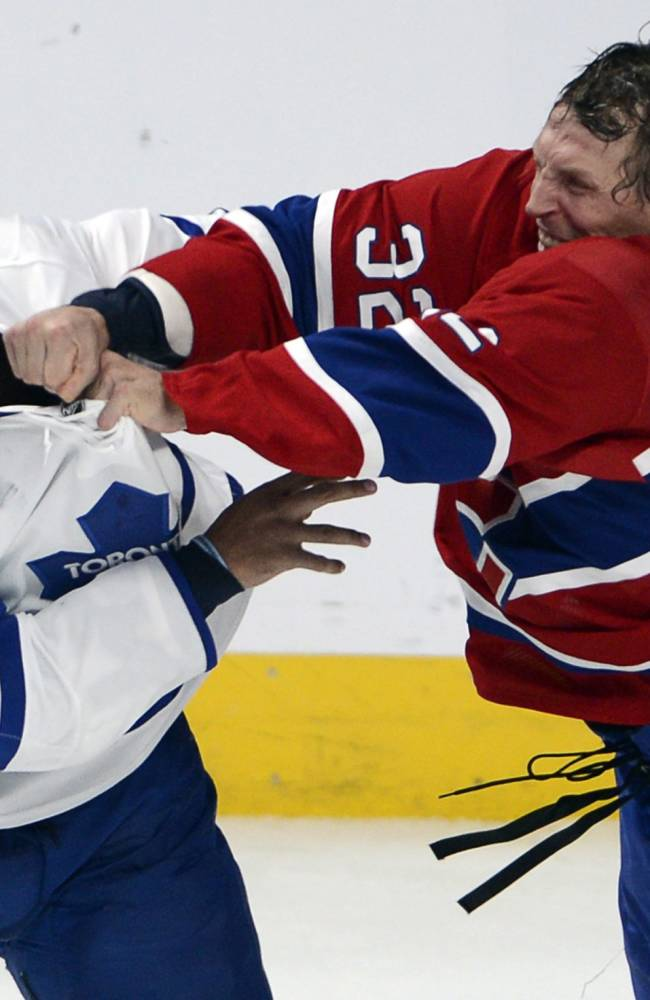 Toronto Maple Leafs defenseman Mark Fraser, left, fights with Montreal Canadiens left wing Travis Moen (32) during second period of an NHL hockey game on Tuesday, Oct. 1, 2013, in Montreal