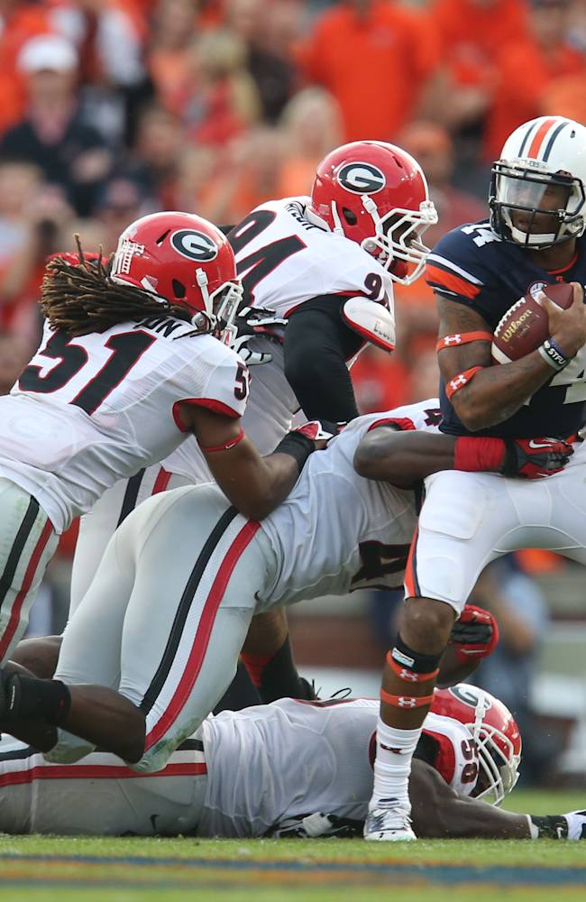 Auburn quarterback Nick Marshall (14) is able to get out of the tackle of Georgia linebacker Ramik Wilson (51), defensive ends John Taylor (94), Ray Drew (47) and Sterling Bailey (58) during the first quarter of an NCAA college football game at Jordan-Hare Stadium on Saturday, Nov. 16, 2013. Auburn won 43-38