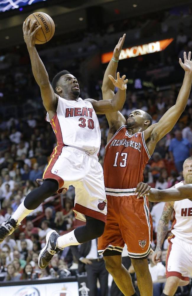 Miami Heat guard Norris Cole (30) goes up to shoot against Milwaukee Bucks guard Ramon Sessions (13) during the first half of an NBA basketball game on Wednesday, April 2, 2014, in Miami