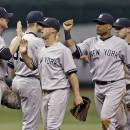 New York Yankees' Lyle Overbay, left, high-fives teammates, from left, Brett Gardner, Robinson Cano, and Jayson Nix after the team defeated the Tampa Bay Rays 9-4 during a baseball game, Friday, May 24, 2013, in St. Petersburg, Fla. (AP Photo/Chris O'Meara)