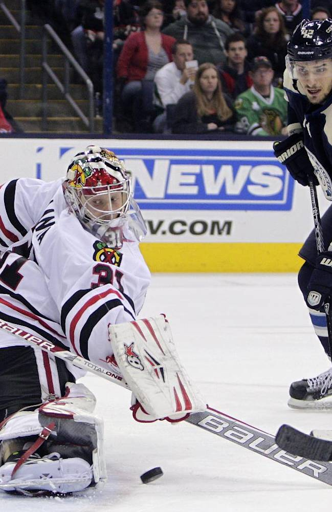 Chicago Blackhawks' Antti Raanta, left, of Finland, makes a save as Columbus Blue Jackets' Artem Anisimov, of Russia, waits for a rebound during the second period of an NHL hockey game on Friday, April 4, 2014, in Columbus, Ohio
