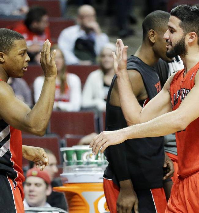 Toronto Raptors guard Kyle Lowry, left, celebrates with Greivis Vasquez, right, on the sideline during the second half of an NBA basketball game against the Chicago Bulls in Chicago on Saturday, Dec. 14, 2013. The Raptors won 99-77