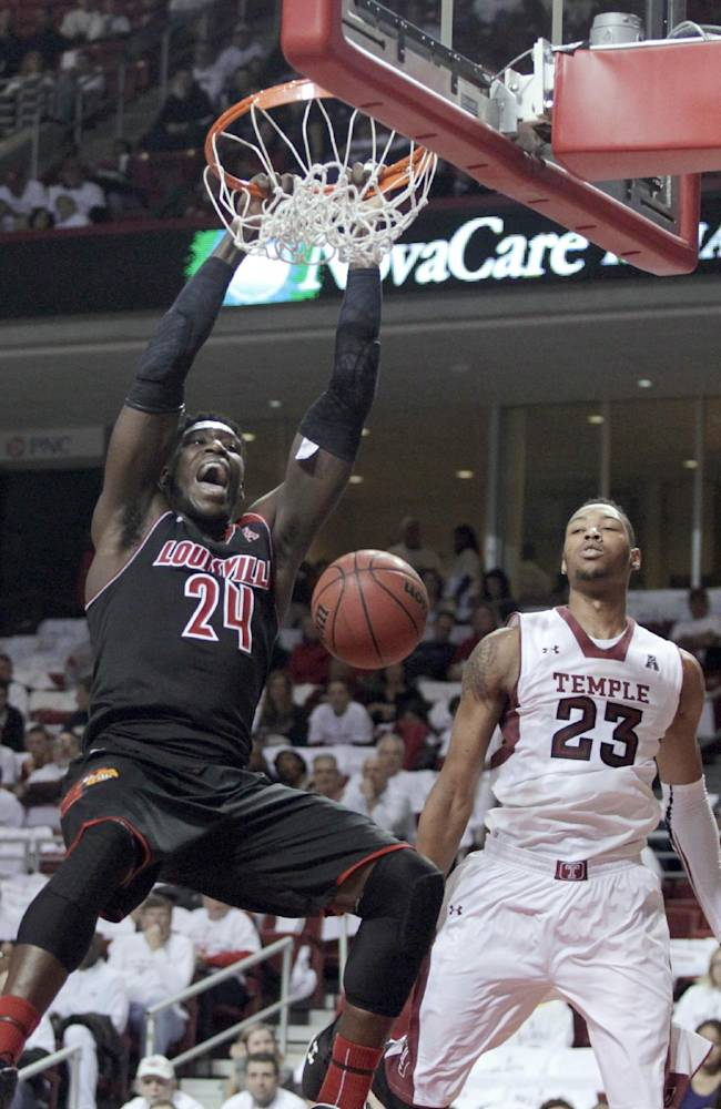 Louisville's Monterzl Harrell (24) scores as Temple's Devontae Watson (23) defends during the first half of an NCAA college basketball game, Friday, Feb. 14, 2014, in Philadelphia