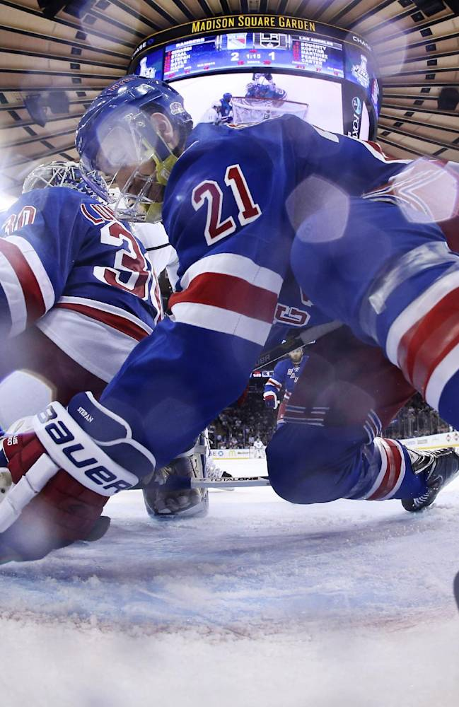 New York Rangers center Derek Stepan (21) reaches to move the puck away from the goal behind goalie Henrik Lundqvist (30) in the third period during Game 4 of the NHL hockey Stanley Cup Final, Wednesday, June 11, 2014, in New York. The Rangers won the game 2-1