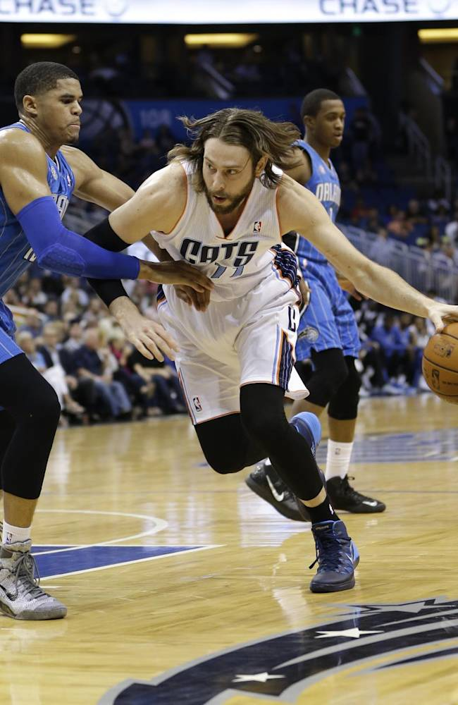 Charlotte Bobcats' Josh McRoberts, right, makes a move to get around Orlando Magic's Tobias Harris, left, during the first half of an NBA basketball game in Orlando, Fla., Friday, March 28, 2014