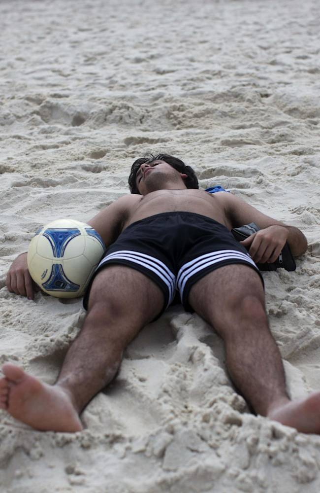 A man sleeps on the sand with a soccer ball at his side on Copacabana Beach in Rio de Janeiro, Brazil, Saturday, July 12, 2014. Argentina will face Germany in the World Cup final, Sunday