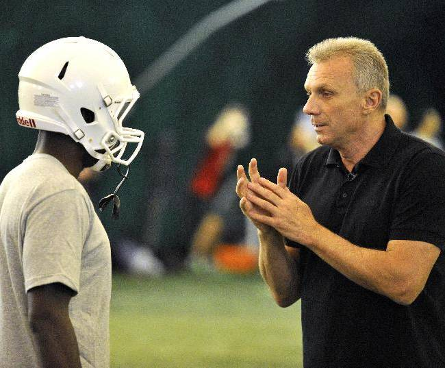 In this image taken on Thursday Oct. 24, 2013 and released by NFL, NFL legend Joe Montana, right, gives instructions during a session with quarterbacks from British universities at Crystal Palace Sports Centre, London. The San Francisco 49ers are due to play the the Jacksonville Jaguars at Wembley stadium in London on Sunday, Oct. 27 in a regular season NFL game