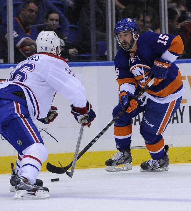 New York Islanders right wing Cal Clutterbuck (15) skates against Montreal Canadiens defenseman Josh Gorges (26) in the second period of an NHL hockey game at Nassau Coliseum in Uniondale, N.Y., Saturday, Dec. 14, 2013