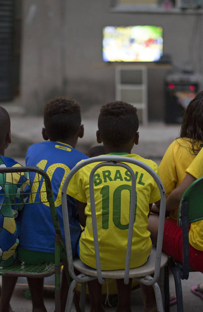 Children watch the World Cup opening match between Brazil and Croatia in an alley at the Mangueira slum, in Rio de Janeiro, Brazil, Thursday, June 12, 2014. After taking the early lead in the opening match of the international soccer tournament, Croatia fell 3-1 to the five-time champion Brazil. (AP Photo/Leo Correa)