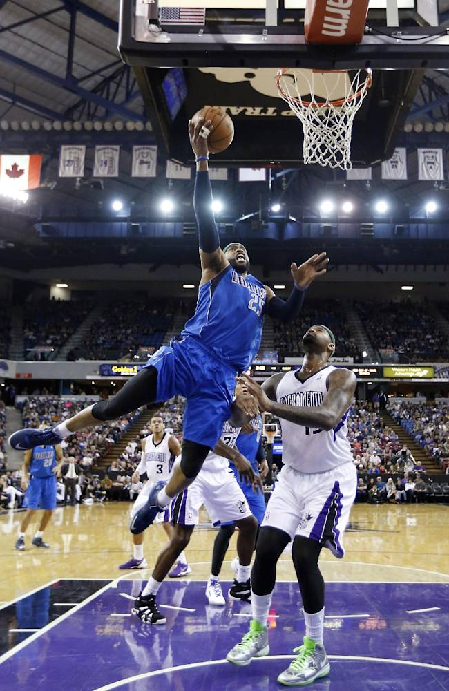 Dallas Mavericks guard Vince Carter, left, goes to the basket against Sacramento Kings center DeMarcus Cousins, right, during the first quarter of an NBA basketball game, Sunday, April 6, 2014, in Sacramento, Calif
