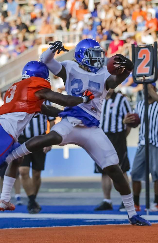 Boise State running back Jay Ajayi (27) scores a touchdown past cornerback Cleshawn Page (3) during an NCAA college football scrimmage n Boise, Idaho, on Friday, Aug. 15, 2014