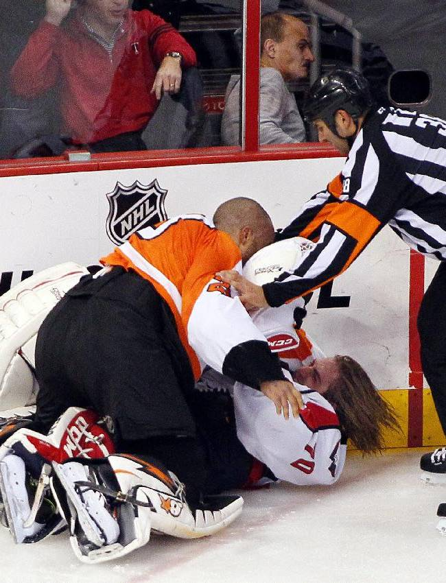 Linesman Francois St. Laurent, right, tries to pull Philadelphia Flyers goalie Ray Emery, top, off of Washington Capitals goalie Braden Holtby during a melee in the third period of an NHL hockey game Friday, Nov. 1, 2013, in Philadelphia. The Capital won 7-0