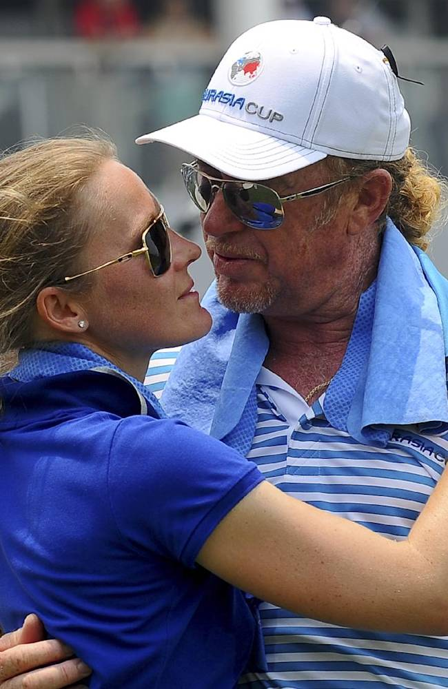 Miguel Angel Jimenez, right, of Spain embraces his girlfriend, Susanne Styblo, after finishing his play on the 18th hole during the second round of the EurAsia Cup golf tournament at the Glenmarie Golf and Country Club in Subang, Friday, March 29, 2014