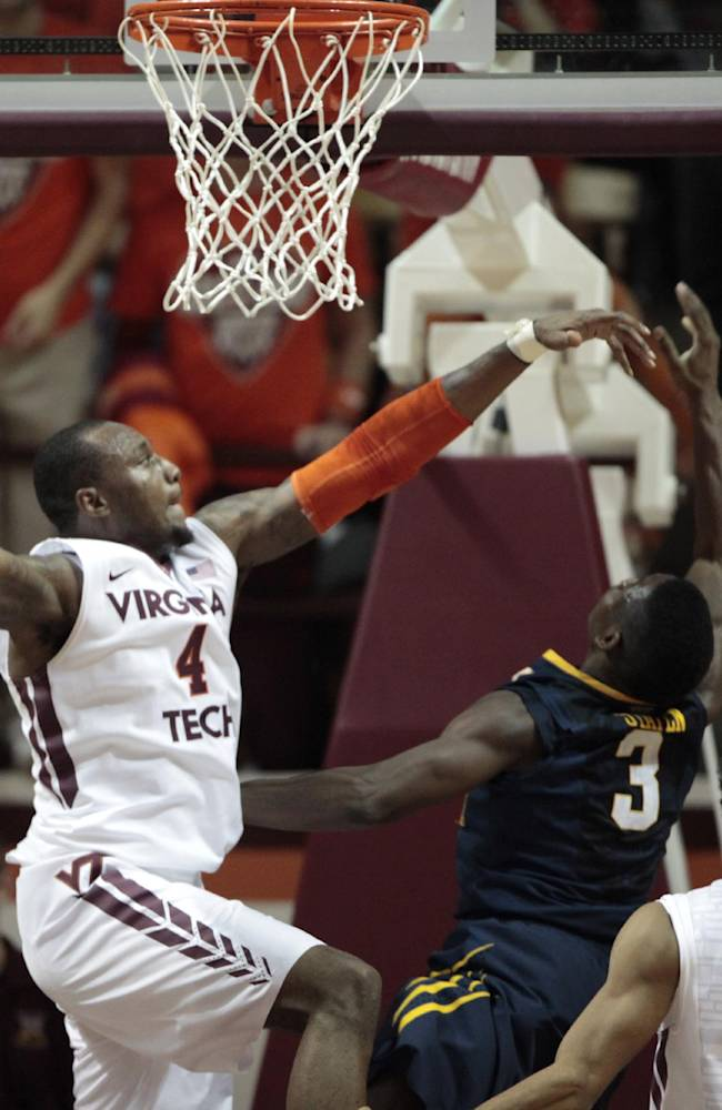 Virginia Tech forward Cadarian Raines (4) blocks a shot from West Virginia guard Juwan Staten (3) during the second half of an NCAA college basketball game in Blacksburg, Va., Tuesday, Nov. 12, 2013