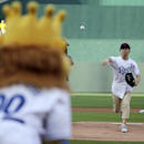 FILE - In this Aug. 11, 2014 file photo, longtime Kansas City Royals fan Sung Woo Lee, from South Korea, throws the ceremonial first pitch before a baseball game against the Oakland Athletics, in Kansas City, Mo. Lee, a die-hard, long-time Kansas City Royals fan from Seoul who became an international celebrity after he was superstitiously credited with sparking the team's playoff run left Tuesday, Oct. 21, for Missouri to watch the Royals appear in their first World Series since 1985. (AP Photo/Charlie Riedel, File)