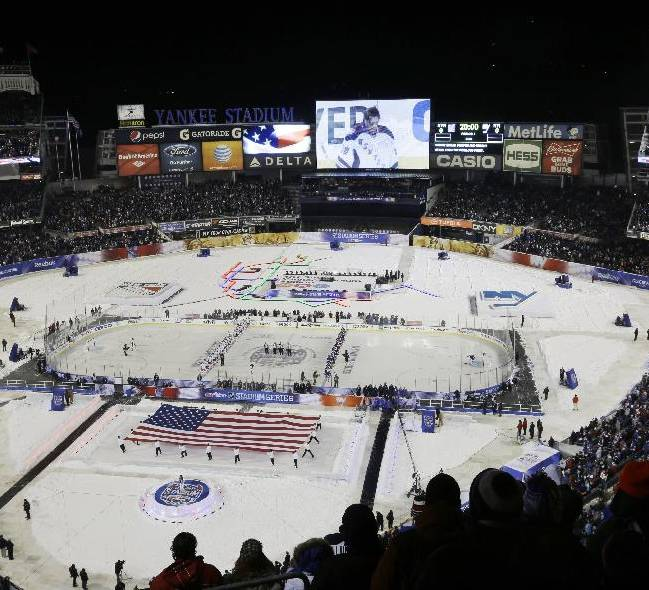 Fans stand during the playing of the national anthems before an outdoor NHL hockey game between the New York Islanders and the New York Rangers Wednesday, Jan. 29, 2014, at Yankee Stadium in New York
