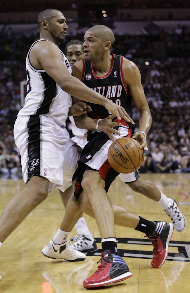 Portland Trail Blazers' Nicolas Batum, right, is pressured by San Antonio Spurs' Boris Diaw, left, of France, during the second half of Game 2 of a Western Conference semifinal NBA basketball playoff series, Thursday, May 8, 2014, in San Antonio. San Antonio won 114-97