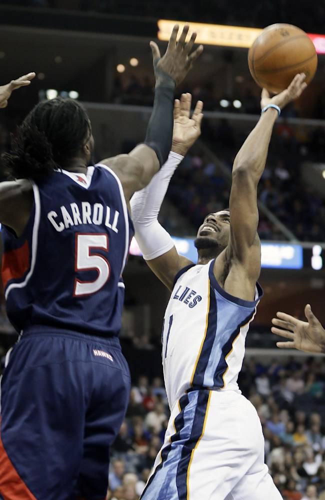 Memphis Grizzlies' Mike Conley, right, shoots over Atlanta Hawks' DeMarre Carroll (5) in the second half of an NBA basketball game in Memphis, Tenn., Sunday, Jan. 12, 2014. The Grizzlies won 108-101