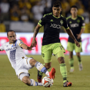 Los Angeles Galaxy midfielder Landon Donovan, left, slides for the ball as Seattle Sounders defender DeAndre Yedlin, right, moves the ball down the field during the second half of an MLS soccer match in Carson, Calif., Sunday, Oct. 19, 2014. The game ende