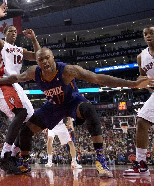 Phoenix Suns guard P.J.Tucker (17) lets out a yell after being fouled while rebounding against Toronto Raptors guards DeMar DeRozan (10) and Kyle Lowry (7) during the first half of an NBA basketball game in Toronto on Sunday, March 16, 2014