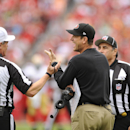 San Francisco 49ers head coach Jim Harbaugh, center, speaks with referee Scott Green, left, and head linesman Tom Stabile during the first half of an NFL football game against the Tampa Bay Buccaneers, Sunday, Dec. 15, 2013, in Tampa, Fla. (AP Photo/Brian Blanco)