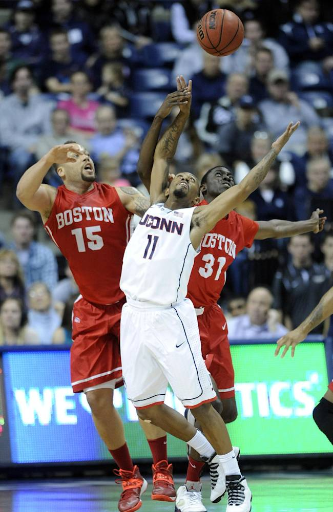 Boston University's Dom Morris (15) and Malik Thomas (31) fight for a rebound with Connecticut's Ryan Boatright (11) during the first half of an NCAA college basketball game in Storrs, Conn., on Sunday, Nov. 17, 2013