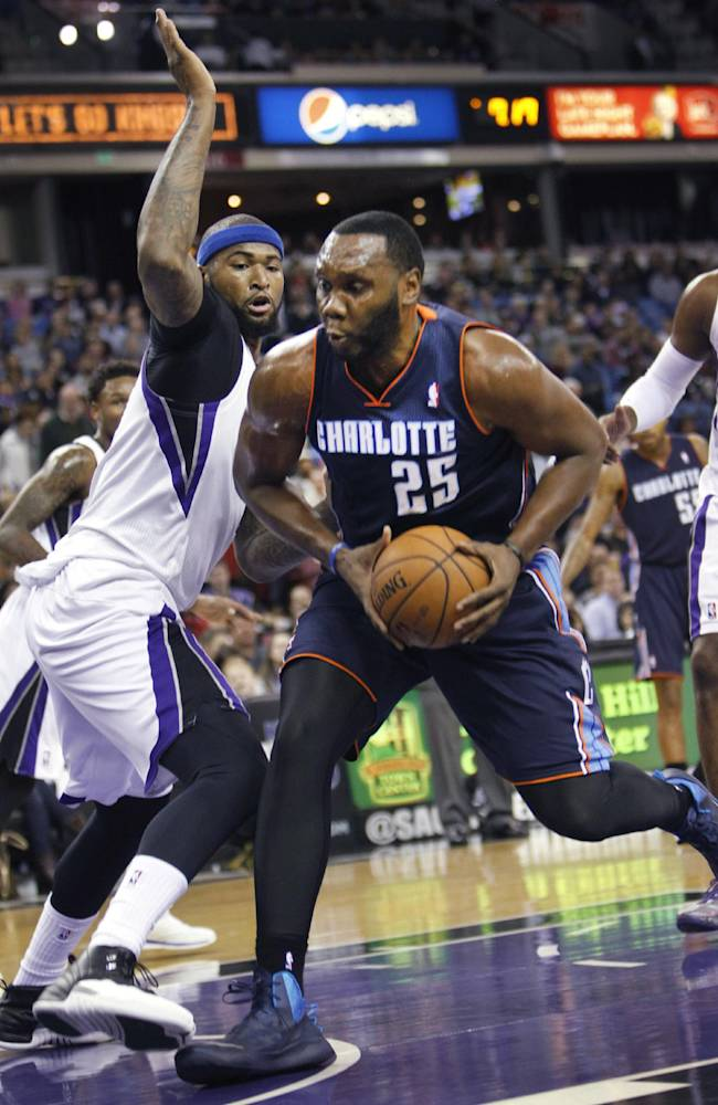 Charlotte Bobcats center Al Jefferson (25) drives to the basket against Sacramento Kings center DeMarcus Cousins during the first half of an NBA basketball game in Sacramento, Calif., on Saturday, Jan. 4, 2014