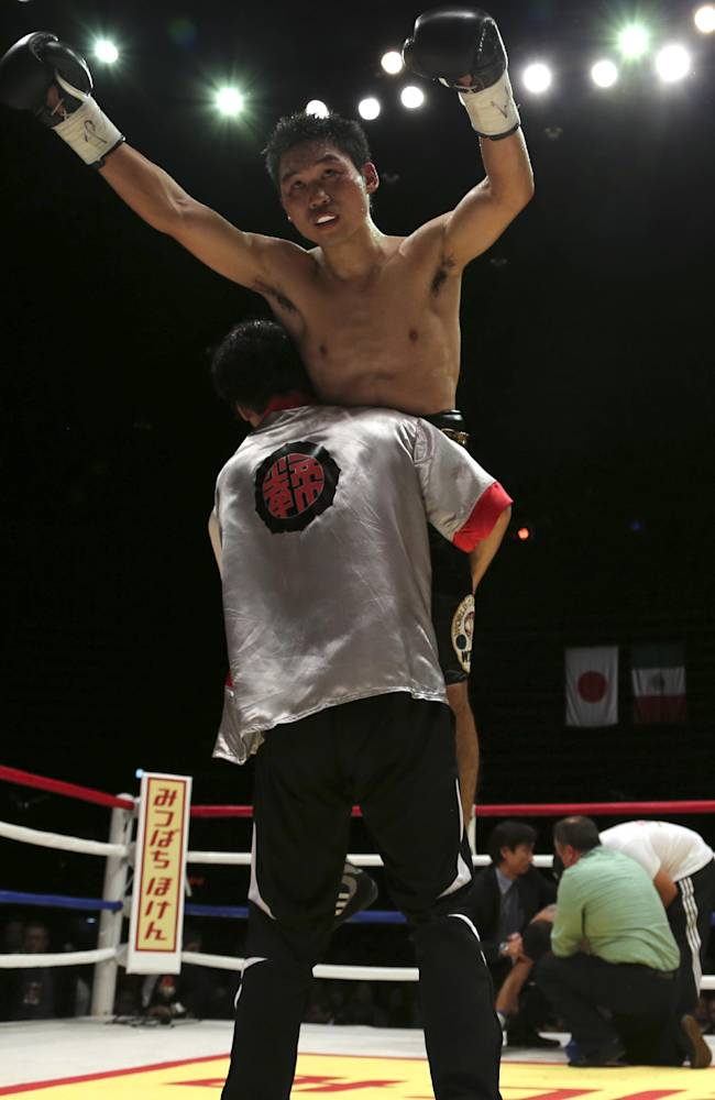 Japanese champion Takashi Miura celebrates after Mexican challenger Dante Jardon, back, was stopped by the referee in the ninth round of their WBC super featherweight title bout in Tokyo, Tuesday, Dec. 31, 2013. Miura defended his title by a technical knockout