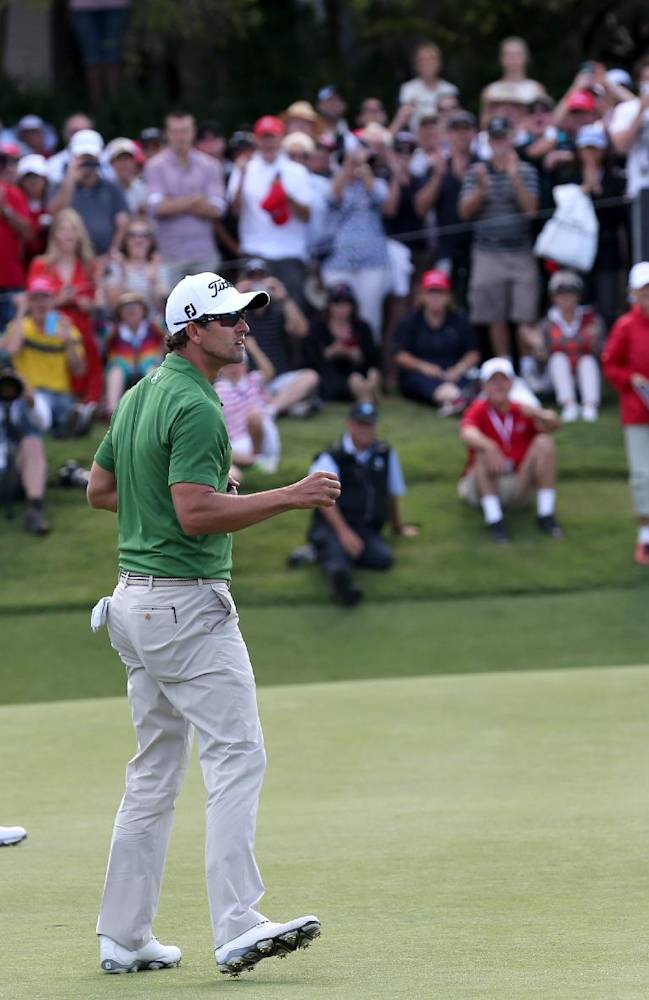 Australia's Adam Scott reacts after sinking a birdie putt on the 18th green as playing partner Rory McIlroy,left, of Northern Ireland looks on during their third round at the Australian Open Golf tournament in Sydney, Australia, Saturday, Nov. 30, 2013