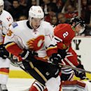 Calgary Flames center Sean Monahan (23) battles for the puck against Chicago Blackhawks defenseman Duncan Keith (2) during the first period of an NHL hockey game in Chicago, Sunday, Dec. 14, 2014 The Associated Press