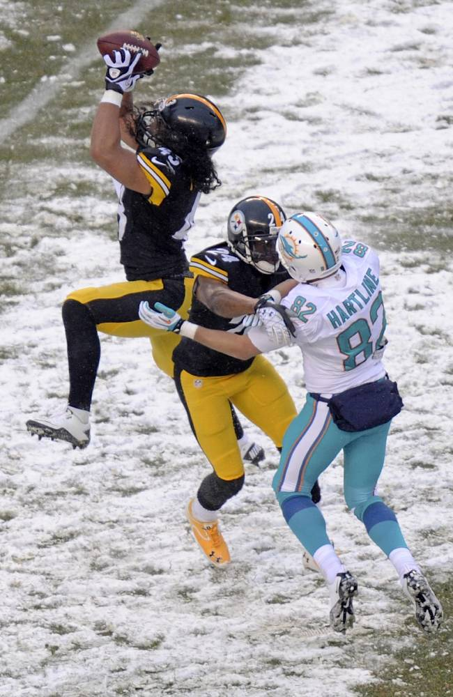 Pittsburgh Steelers strong safety Troy Polamalu , left,  intercepts a pass intended for Miami Dolphins wide receiver Brian Hartline (82) and returns it for a touchdown during the second half of an NFL football game in Pittsburgh, Sunday, Dec. 8, 2013