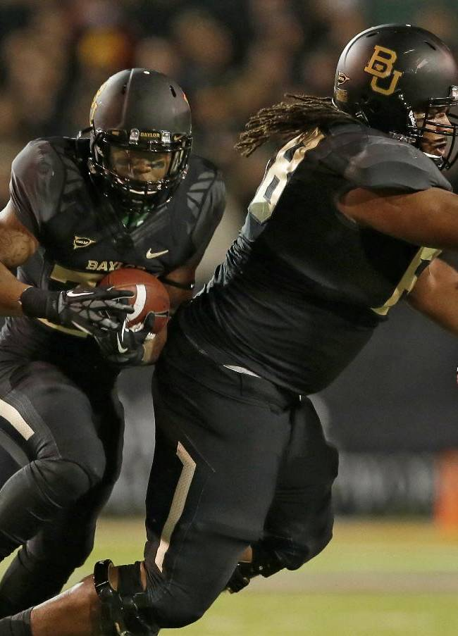 Baylor running back Shock Linwood (32) finds a gap behind guard Cyril Richardson (68) who fights off pressure from Oklahoma defensive end Charles Tapper (91) as Oklahoma's Gabe Lynn, left, helps on the tackle attempt in the first half of an NCAA college football game, Thursday, Nov. 7, 2013, in Waco, Texas