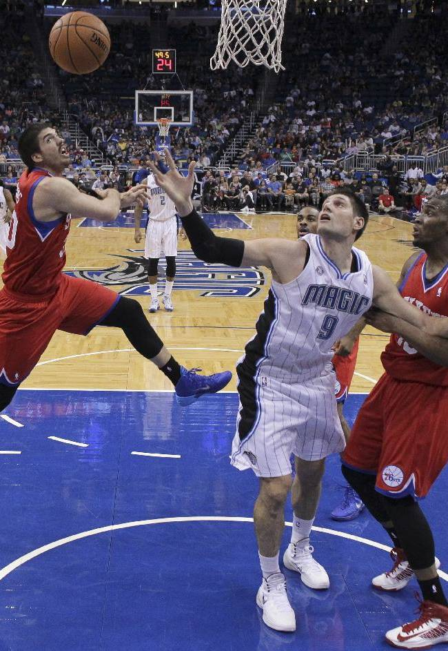 Orlando Magic's Nikola Vucevic (9) goes after a rebound against Philadelphia 76ers' Byron Mullens, left, and Jarvis Varnado during the first half of an NBA basketball game in Orlando, Fla., Sunday, March 2, 2014