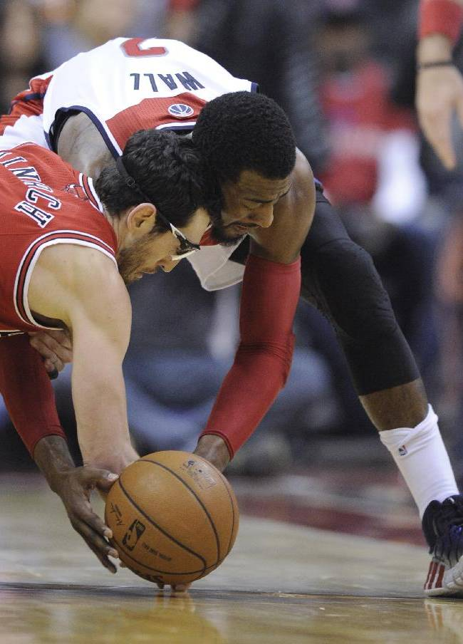 Washington Wizards guard John Wall, right, scrambles for the ball against Chicago Bulls guard Kirk Hinrich during the second half of an NBA basketball game, Saturday, April 5, 2014, in Washington. The Bulls won 96-78