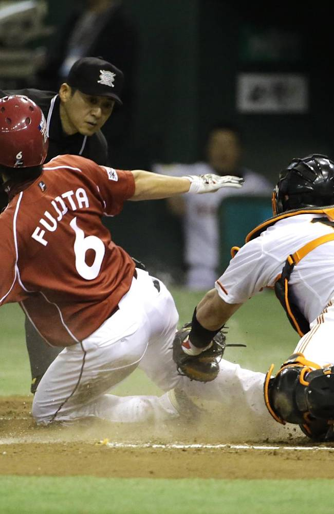 Yomiuri Giants catcher Shinnosuke Abe cannot tag out as Rakuten Eagles' Kazuya Fujita (6) scores on an RBI single by Andruw Jones in the eighth inning of Game 3 of baseball's Japan Series at Tokyo Dome in Tokyo, Tuesday, Oct. 29, 2013