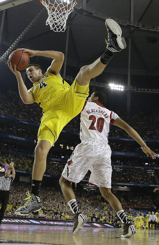 In this April 8, 2013 file photo, Michigan forward Mitch McGary (4) comes down with the rebound as Louisville guard/forward Wayne Blackshear (20) looks on during the first half of the NCAA Final Four tournament college basketball championship game in Atlanta. McGary is entering the NBA draft, saying he had little choice after testing positive for marijuana during the NCAA tournament.