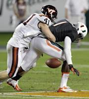 Miami wide receiver Artie Burns (1) fumbles the ball as he is tackled by Virginia Tech's Derek DiNardo (41) during the first half of an NCAA college football game, Saturday, Nov. 9, 2013, in Miami Gardens, Fla. (AP Photo/Wilfredo Lee)