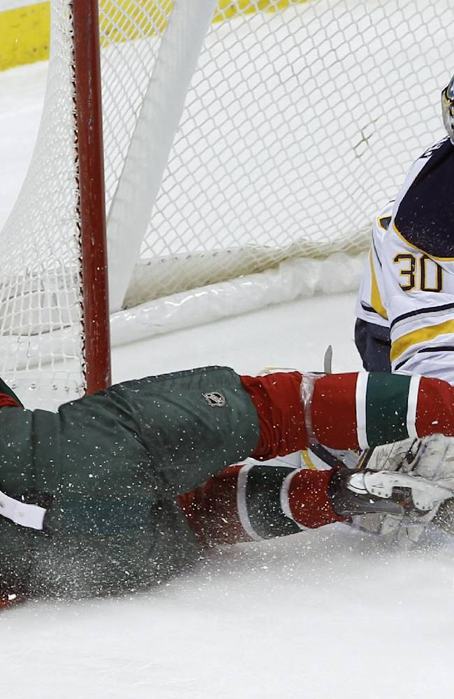 Buffalo Sabres goalie Ryan Miller (30) deflects a shot by falling Minnesota Wild center Mikko Koivu (9), of Finland, during the first period of an NHL hockey game in St. Paul, Minn., Thursday, Jan. 2, 2014