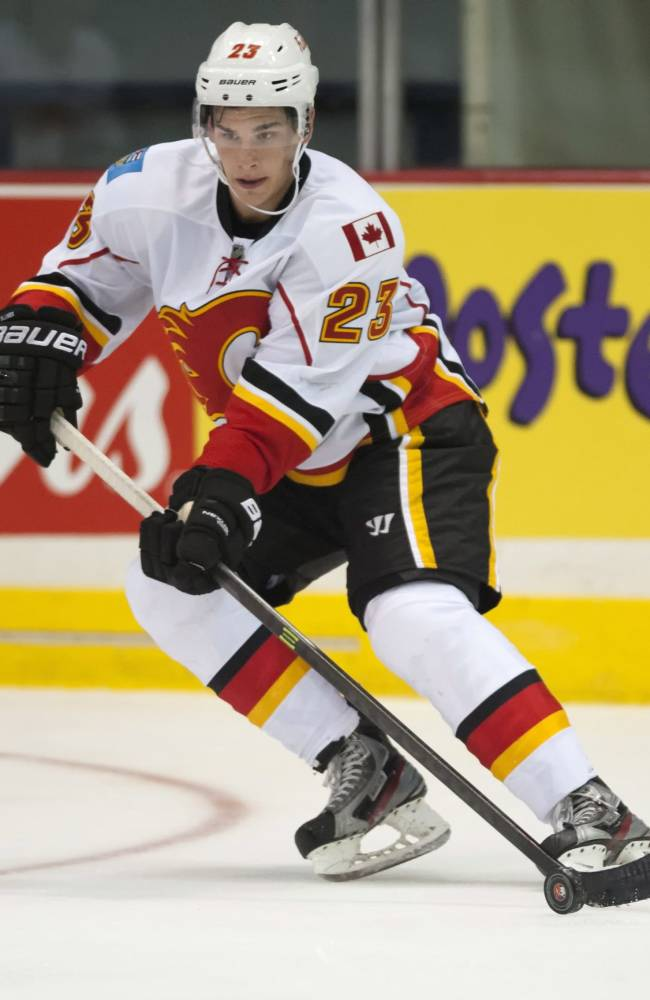 Calgary Flames forward Sean Monahan moves the puck against the New York Islanders during the third period of an NHL hockey game Tuesday, Sept. 17, 2013, in Regina, Saskatchewan. The Flames won 4-2