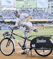 New York Yankees' Mariano Rivera tries out his new beach bike given to him by the San Diego Padres in a ceremony preceding the baseball game between the Yankees and Padres in San Diego, Friday, Aug. 2, 2013. (AP Photo/Lenny Ignelzi)
