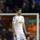 Swansea's Federico Fernandez makes his way from the pitch after being sent off by referee Keith Stroud, during the English League Cup soccer match between Liverpool and Swansea at Anfield Stadium, Liverpool, England, Tuesday Oct. 28, 2014